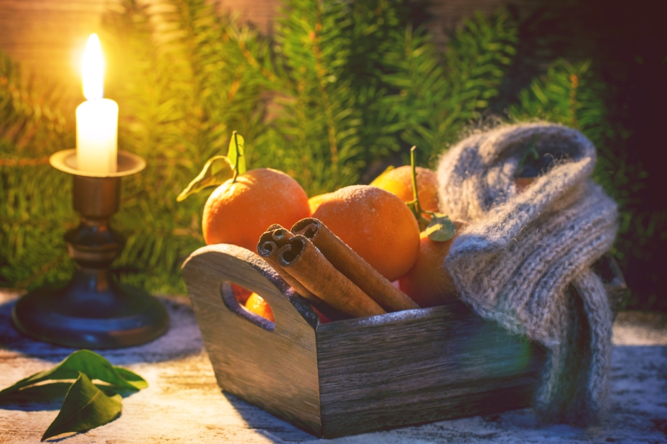 Wooden basket with tangerines, cinnamon sticks and scarf over wooden background with burning candle, snow and Christmas tree.
