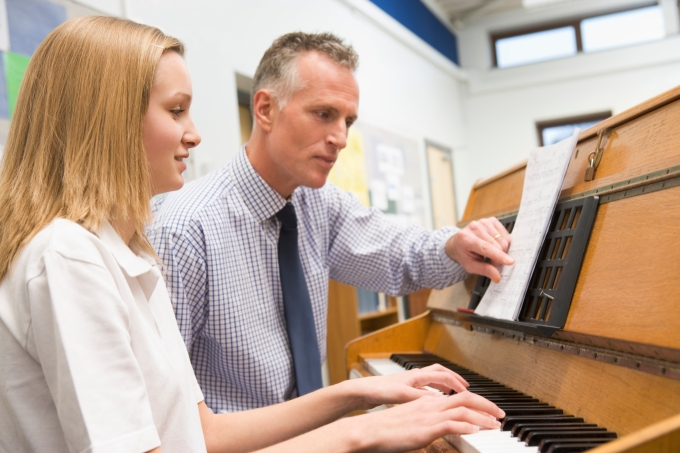 Teacher and student working on piano music